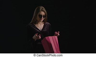 Woman Black Friday Shopping - Happy woman open red bag on...
