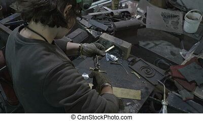 Woman blacksmith crafting a piece of aluminum metal in her...