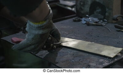 Woman blacksmith cutting a piece of aluminum using wire...