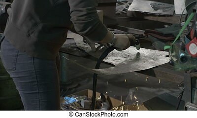 Woman blacksmith cutting aluminum shapes with plasma cutter...