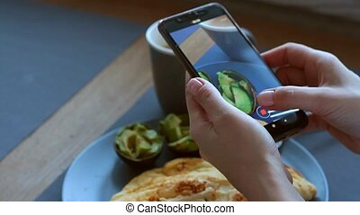 Woman blogger takes breakfast of omelet and avocado on her smartphone, ketogenic nutrition, real life, selective focus