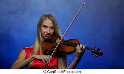 Woman blonde plays the fiddle. Smoky background. Slow motion...