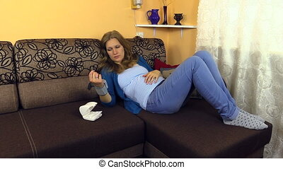 woman blood pressure - Tired pregnant woman lie on couch...