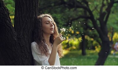 Woman Blow on a Dandelion - Woman blowing dandelion seeds at...