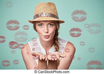 Woman blowing a kiss - Beautiful woman wearing summer straw...