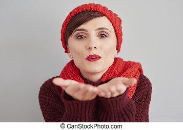 Woman blowing a kiss towards the camera