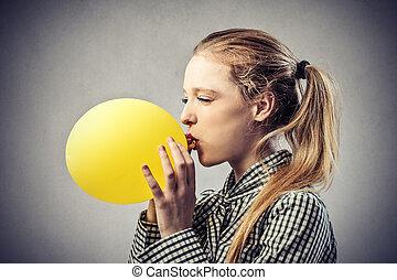 Woman blowing balloon - Woman blowing yellow balloon