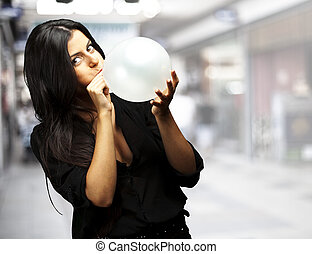 woman blowing balloon - portrait of young woman blowing...