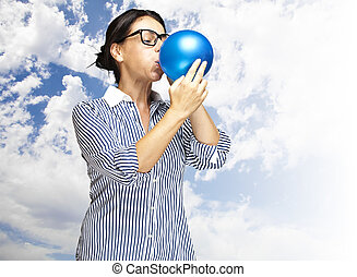 woman blowing balloon - portrait of middle aged woman...