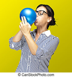 woman blowing balloon - portrait of a middle aged woman...