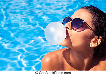 Woman blowing bubble with gum - Charming woman in sunglasses...