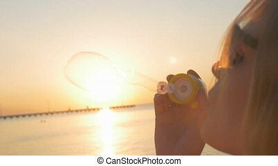 Woman blowing bubbles on the beach at sunset