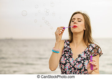 Woman blowing bubbles outdoor