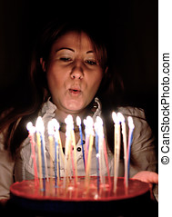 woman blowing candle on birthday cake