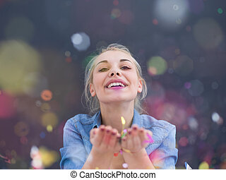 woman blowing confetti in the air isolated over gray