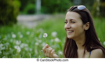 Woman Blowing Dandelion on a Summer Field