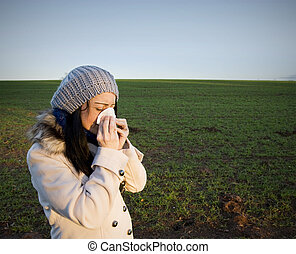 Woman blowing nose - A Woman in countryside blowing her nose