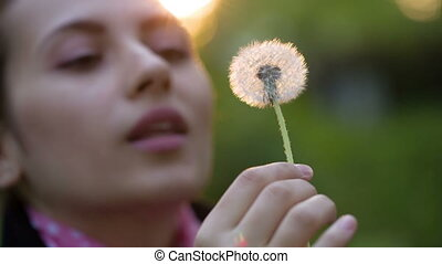 Woman Blowing on a Dandelion