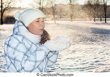 Woman blowing on snow in hands with mittens