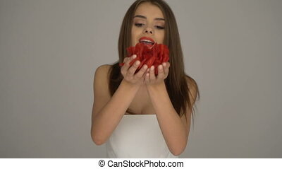 Woman blowing red rose petals