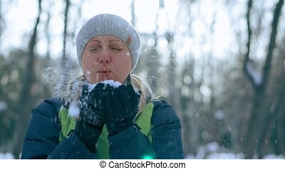 woman blowing snow in a winter park, having silly fun, smiling.
