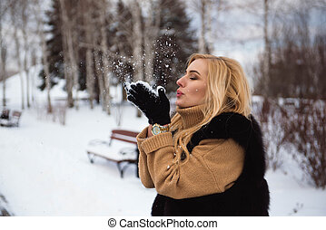 woman blowing snow in hands in slow motion. - woman blowing...