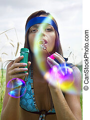 woman blowing soap bubble - wistful young woman blowing soap...