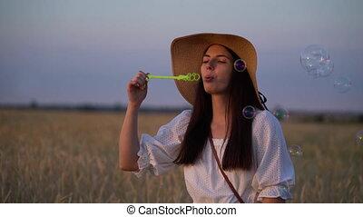 Woman blowing soap bubbles in field.
