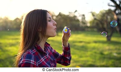 Woman blowing soap bubbles outdoors - slow motion