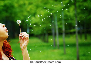 Woman blows away a dandelion among the trees