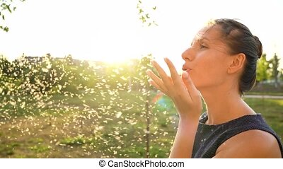 Portrait of smiling woman blowing on reeds and fluff flies around her outdoors in sunny day
