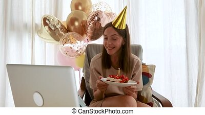 Woman blows out candle on cake in front of laptop while ...