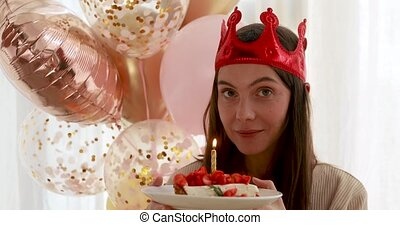 Woman blows out the candle on the cake - Portrait of a young...