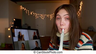 Brunette woman blows party horn celebrating birthday with friends via video chat on laptop in decorated room at quarantine
