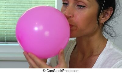 Woman blows the balloon close up