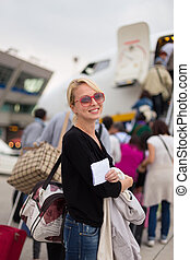 Woman boarding airplane. - Cheerful woman holding carry on...