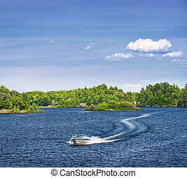 Woman boating on lake - Woman piloting motorboat on lake in...