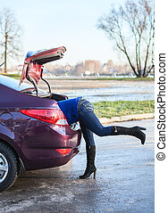 Woman body into car luggage trunk. Legs sticking out