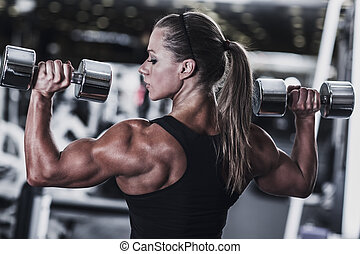 Woman bodybuilder - Young woman bodybuilder with dumbbells.