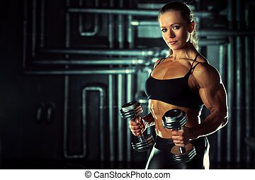 Woman bodybuilder with dumbbells on wall background.