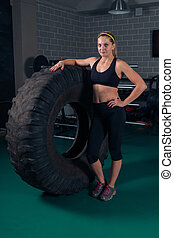 Woman bodybuilding. Fitness woman posing near the tire in the gym