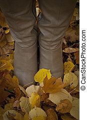 Woman boots standing on autumn leaves - Walk concept