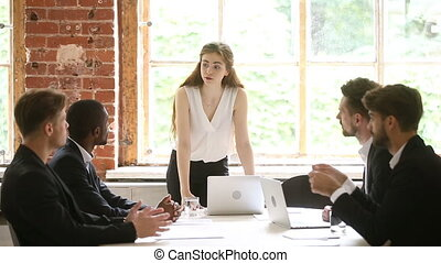 Woman boss discussing project at group meeting with diverse...