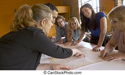 Woman boss shows her employees the architectural plans for a new building