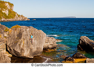 Woman bouldering on the shoreline of Georgian Bay