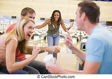 Woman bowling with friends