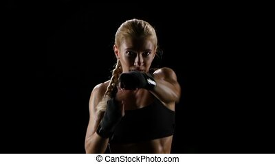Woman boxer training herself in a dark studio. Slow motion