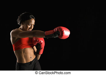 African American young adult woman wearing boxing gloves throwing punch.
