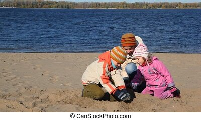 woman, boy and girl constructing sand buildings