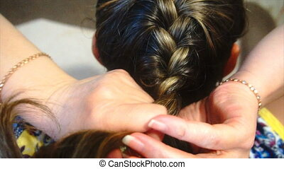 woman braids pigtails herself, slow motion - woman braids...